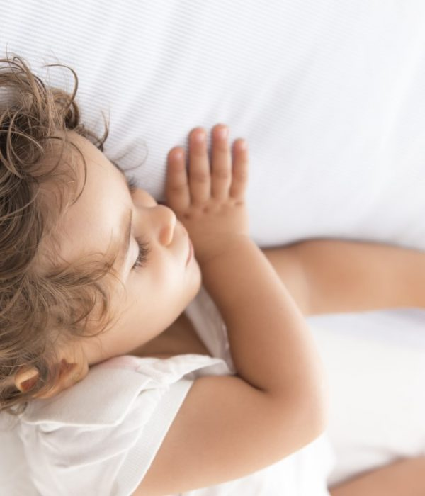 Serene and cute baby sleeping on a pillow in the bed